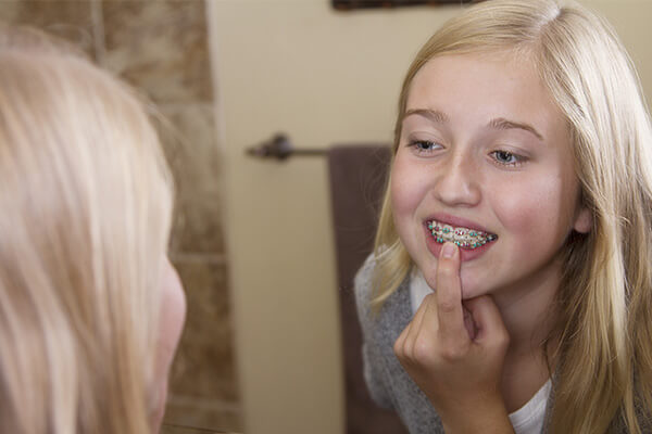 girl checking out braces